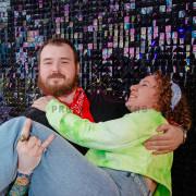 Пара фотографируется на фоне фотозоны из пайеток